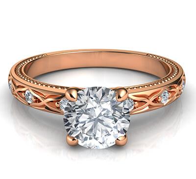Anillo de compromiso de estilo vintage con motivos de hojas y diamantes laterales.